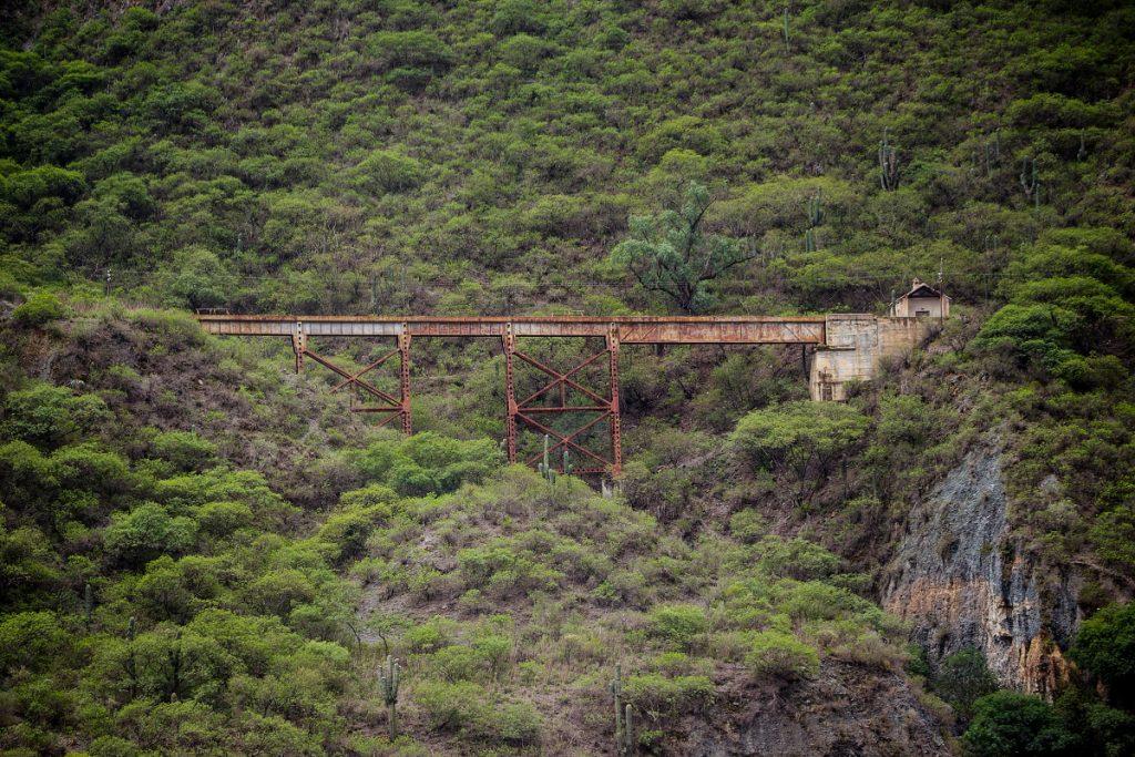 Železniční most s domkem na úbočí kopce